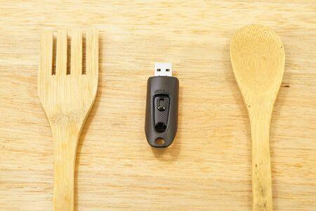 Eet gegevens - USB-flashstation op de houten achtergrond met lepel en vork.