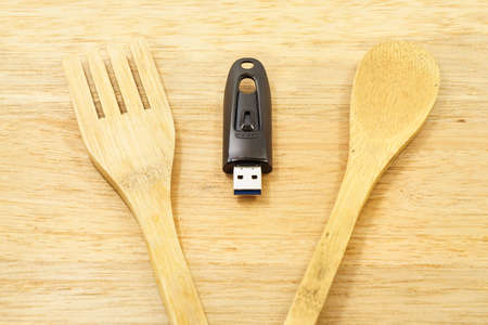 usb flash drive: Eat data - usb flash drive on the wood background with spoon and fork.