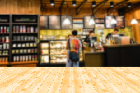 Wood table top with blur background of coffee shop