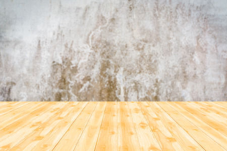 Wood table top with blur background of concrete wall