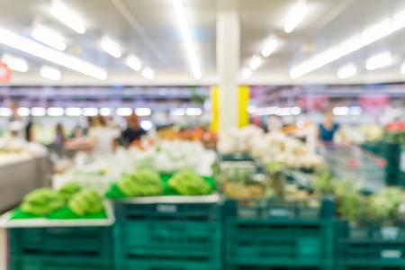 Verschwommene abstrakten Hintergrund des Menschen beim Einkaufen im Supermarkt: Käufer im Supermarkt in einem Gang: Gehweg mit voll mit Waren und Produkte im Regal im Supermarkt