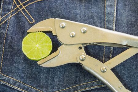 locking: locking Pliers and lime put on jeans background.