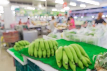 スーパー マーケットでのショッピングの人々 の抽象的な背景がぼやけ: 渡り板の食料品店で買い物: 商品とスーパー マーケットで棚に製品で完全に