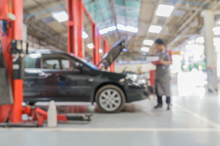 automotive industry: Blurred of car technician repairing the car in garage background. Stock Photo