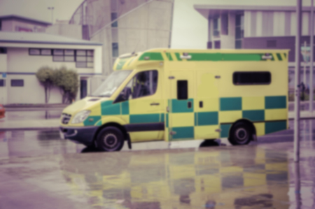 working accident: blurred background of An ambulance speeding through the streets.in vintage color effect.
