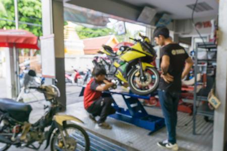 バック グラウンド駐車場でバイクを修理オートバイ技術者のぼやけています。