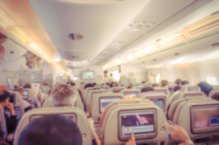 Blurred background of  interior aircraft , flight attendant helping passenger to put luggage cabin compartment.in vintage color effect.