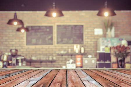 shop interior: Wood table top with coffee shop blur background with bokeh image,in vintage effect - can be used for montage or display your products