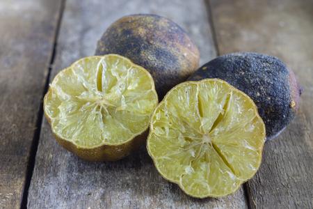 perishable: mold lemons,rotten lemon,rotten lime on wooden background.