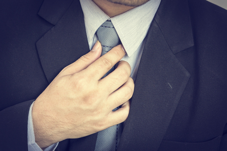 homem de negócios que toca em sua gravata. Fim acima, retrato do close up do homem de negócios no colarinho da camisa azul e terno com laço.