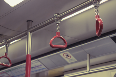 Handle on ceiling of bus,handle on a train,The handle on the MRT, prevent toppling.underground railway system or metro Imagens - 48178463