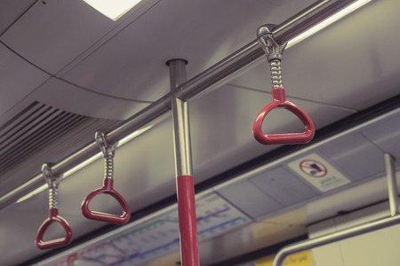 gripping bars: Handle on ceiling of bus,handle on a train,The handle on the MRT, prevent toppling.underground railway system or metro Stock Photo