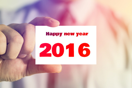 new years resolution: businessman showing business card with happy new year 2016  message on the card shown by a man, vintage tone.