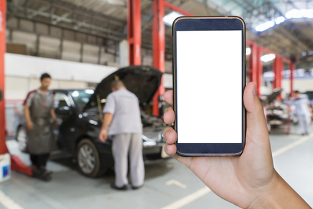 car breakdown: closeup of man with broken car and smart phone, Man hand holding mobile smart phone , tablet,cellphone over Blurred of car technician repairing the car in garage background.