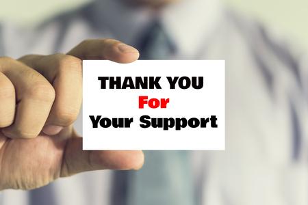 ビジネスマンの男、ビンテージ トーンが示すカードありがとう応援メッセージ付きの名刺を示します。