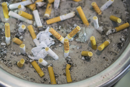 discarded: Discarded cigarette butts,Cigarette butts discarded in ashtray,Cigarette butts stacked,selective focus.
