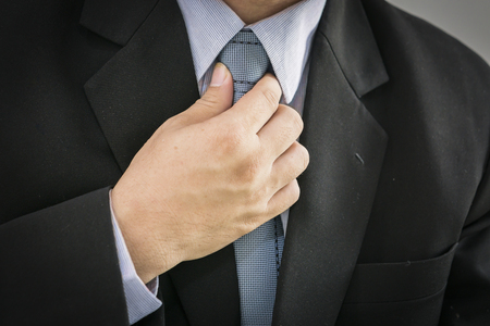 collar shirt: business man touching his tie. Close up,Closeup portrait of businessman in blue collar shirt and suit with tie. Stock Photo