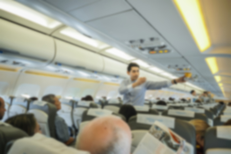 airline hostess: blurred background of air hostess and  Stewart shows how to use an oxygen mask on board,vintage color