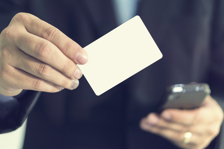 businessman showing business card ,Mans hand showing business card ,closeup shot,selective focus.