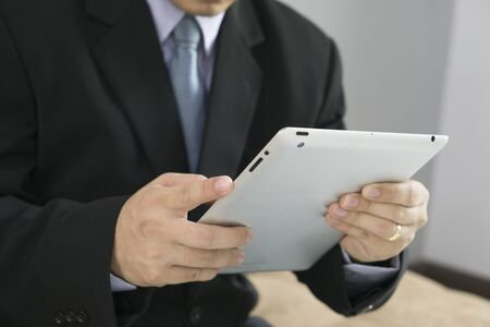 use: Asian Business man use tablet pc Stock Photo
