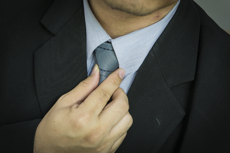 blue collar: business man touching his tie. Close up,Closeup portrait of businessman in blue collar shirt and suit with tie. Stock Photo