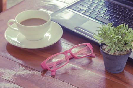 coffee breaks: Time to relax, rest breaks, on the desk, Freelance. A cup of coffee, laptop, green trees. Stock Photo