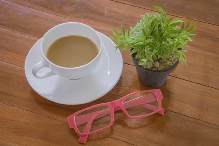coffee breaks: Time to relax, rest breaks, on the desk, Freelance. A cup of coffee,green trees,eyeglasses