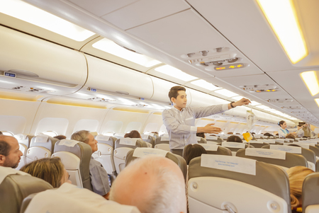 arrière-plan flou de l'hôtesse de l'air et Stewart montre comment utiliser un masque à oxygène à bord, couleur cru