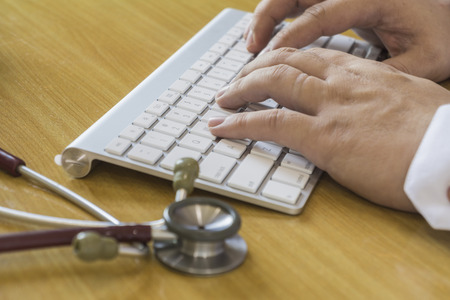teclado: cuidado de la salud, hospital y concepto de la medicina - médico escribiendo masculina en el teclado, teclado de tipo médico con estetoscopio, foco selectivo, el color de la vendimia. Foto de archivo