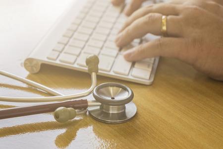 klawiatury: opieki zdrowotnej, szpital i medycyny koncepcji - mężczyzna lekarz pisania na klawiaturze, typ klawiatury Lekarz z stetoskop, selektywne fokus, rocznika koloru. Zdjęcie Seryjne