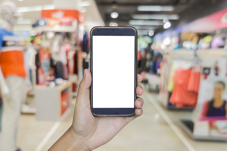 Man hand holding mobile smart phone on  Blur of city shopping people crowd at marketplace shoe shop or sportsshop abstract background, business concept. Stock Photo