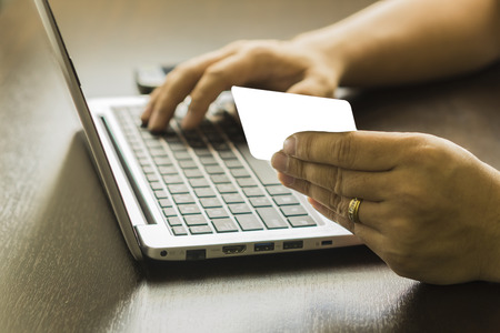Close Up Of A Man Shopping Online Using Laptop With Credit Card,male hands holding credit card typing numbers on computer keyboard while sitting at home at the wooden table,selective focus and vintage color. Banco de Imagens