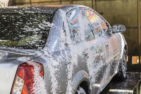 autolavado: Coche que se lava a mano usando una preparación de espuma para pulir, los coches en un tren de lavado, enfoque selectivo Foto de archivo