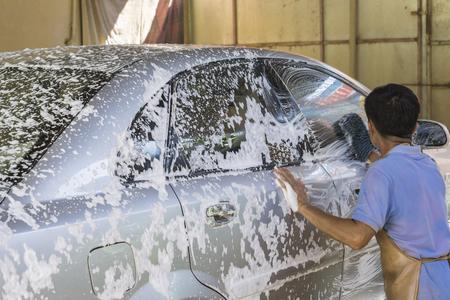 auto lavado: Coche que se lava a mano usando una preparación de espuma para pulir, los coches en un tren de lavado, enfoque selectivo Foto de archivo