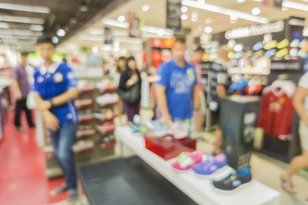 sports equipment: Blur of city shopping people crowd at marketplace shoe shop abstract background.