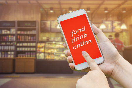 Hand holding mobile with Order food online with blur restaurant and coffee shop background, food and drink online business concept.Leave space for adding your text,vintage color.