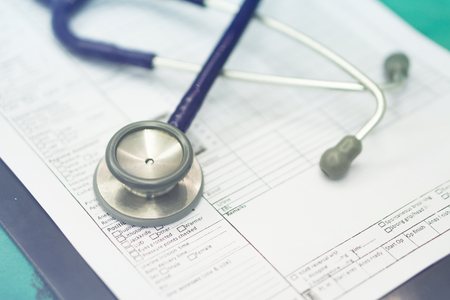 stethoscope prescribing treatment to patient for doctor with pen writing recipe on clipboard in hospital.selective focus ,and blue tone Stock Photo - 56083622