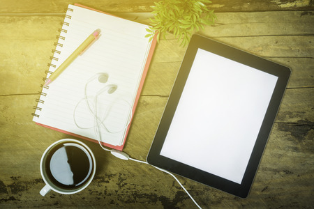 ear phone: Digital tablet with blank screen and a cup of coffee ear phone flower pot on the desk in coffee shop cafe,an office tablet with blank white screen ready for content text ,vintage tone,selective focus. Stock Photo