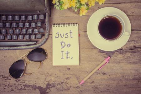 Bovenaanzicht van een geopende laptop met Just do it word tekst op houten achtergrond, Lege nota boek met koffie, glazen, bloempot en pen-kan gebruikt worden voor montage en typ uw tekstbericht, vintage toon.