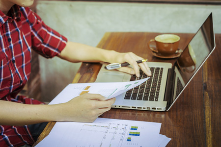 Modern young employee analyzing financial data in office,businessman sitting in front of net book in office,analyzing financial chart,writing business plan ,working on his laptop in a coffee shop Imagens - 56084101