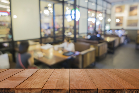 Empty brown wooden table and Coffee shop interior with some people meeting blur background with bokeh image, for product display montage,can be used for montage or display your products Imagens