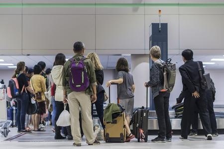 バッグとケースと乗客待ちの収集、選択と集中で空港ターミナルの荷物ベルト、空港の荷物コンベア ベルトにスーツケースを拾うため人つか