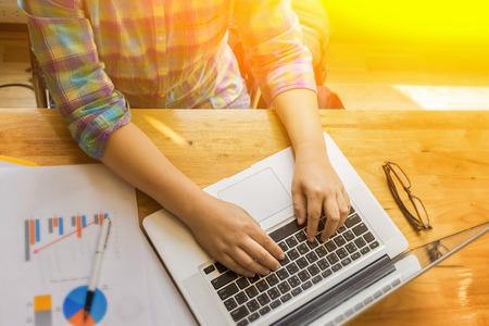 Empresario busca en los datos financieros con gráficos y gráficos, mientras que el trabajo en una computadora portátil, joven empresario analizar su cuaderno, hombre de negocios freelance en el café, enfoque selectivo, el color de la vendimia Foto de archivo