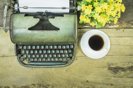 昔のテーブル、木製の板、タイプライターと紙と花のポット、ビンテージ トーン、選択と集中の空白のシート上に配置レトロ タイプライターにレト