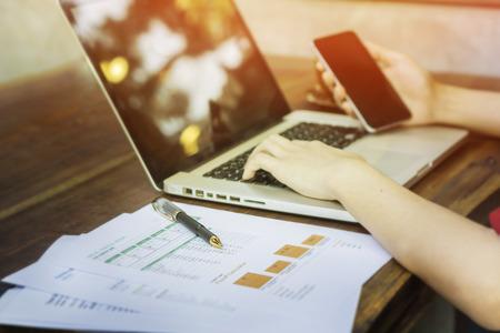 ペーパーおよび金融データ ビジネスマンのオフィスのテーブルの上にペンが、背景、選択と集中、ビンテージ トーンにデータを検索するための携帯