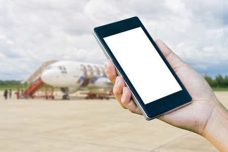 flight mode: Hand Checking-In For A Flight Using Cellphone, hand holding mobile phone with flight mode in the airplane,phone in the hand with a blank screen and blurred a plane in the background Stock Photo