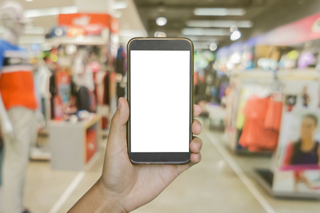 Man hand holding mobile smart phone on  Blur of city shopping people crowd at marketplace shoe shop or sportsshop abstract background, business concept.vintage color.