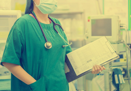 female doctor with stethoscope on hospital corridor holding clipboard  with an operating room at the background ,Healthcare and medical concept,selective focus.vintage tone color Imagens - 56084282