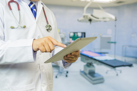 Doctor use tablets computer,Medical Diagnosis And prepare for surgery,doctor recording in Digital clipboard for diagnosis disease,Health Check with digital system support for patient,selective focus
