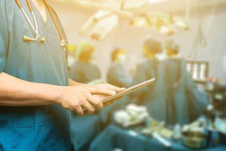 egészségügyi: Férfi orvos, orvostanhallgatók vagy sebész digitális tábla és laptop a konferencia során, állapotfelmérés digitális rendszer támogatja a beteg, a vizsgálati eredmények és a beteg regisztrációs, szelektív összpontosít
